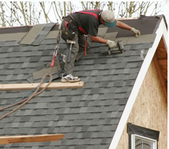 Man pulling shingles from roof